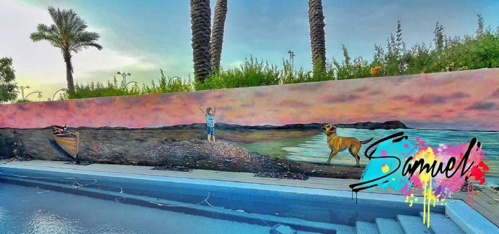 על קיר חיצוני כלב וילד משחקים בחוף הים